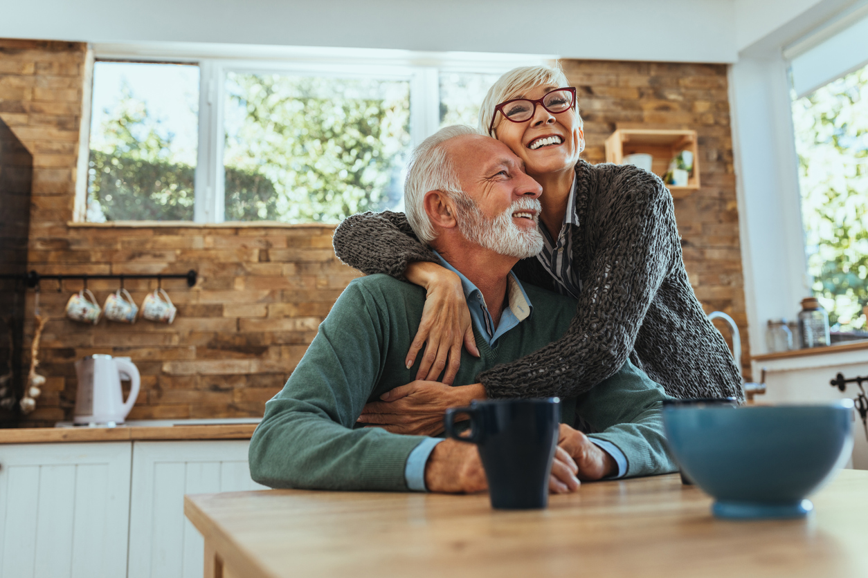 older couple sitting in the kitchen and hugging