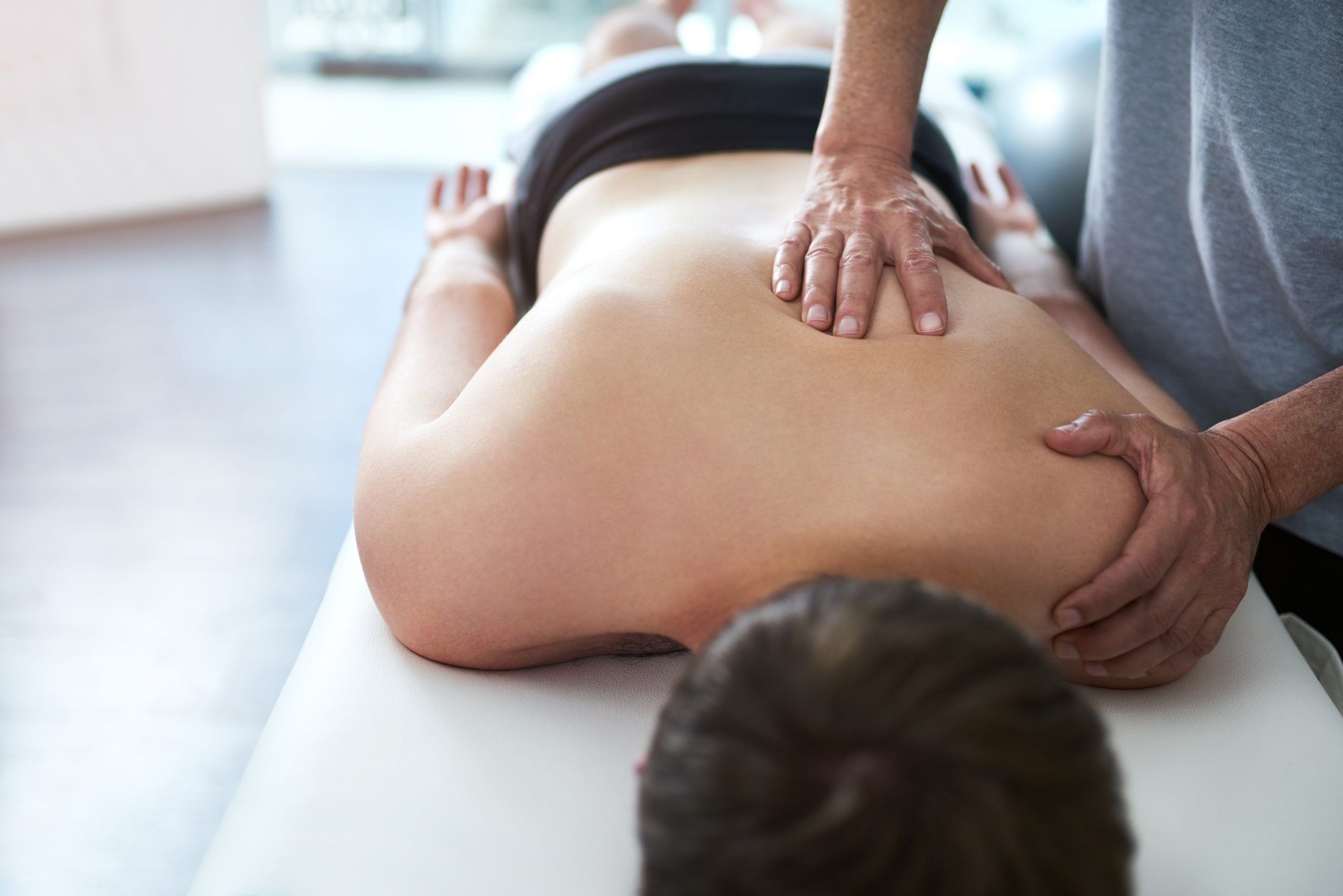 Physiotherapist or massage therapist performing soft tissue work on a patient's back during a visit at Absolute Health and Wellness in Paris Ontario